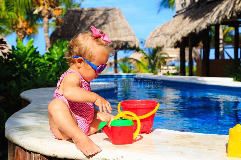 Het leuke peutermeisje spelen in zwembad bij stock afbeeldingen