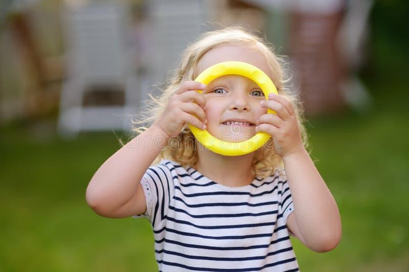Het leuke portret van het peutermeisje in openlucht in de zomerdag Kind het spelen in spel die ringen in openlucht werpen bij de  royalty-vrije stock foto