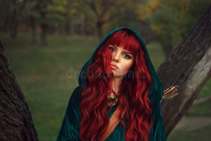 Het leuke roodharige meisje, onderzoekt de camera met bruine ogen, die een smaragdgroene regenjas met een kap op haar hoofd drage stock foto's