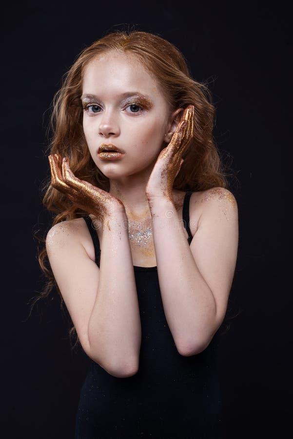 Het leuke roodharige tienermodel met heldere make-up en kleurrijk schittert en fonkelingen op haar gezicht en lichaam stock afbeeldingen
