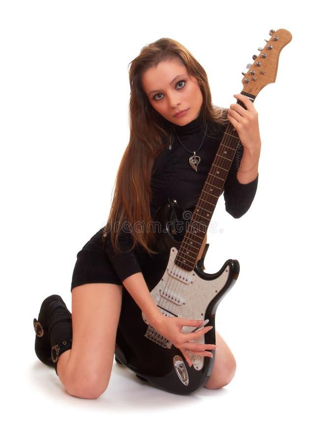 Het leuke rotsmeisje stelt met een elektrische gitaar royalty-vrije stock foto's