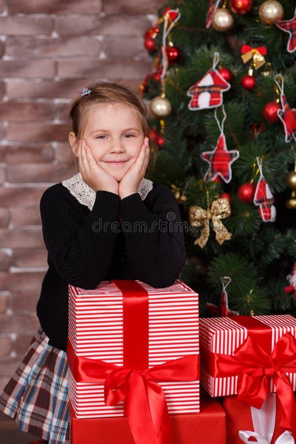 Het leuke smaakvolle meisje die modieuze gelukkige vrijetijdskleding dragen geniet van de vakantie van de Kerstmistijd dicht bij  stock afbeelding