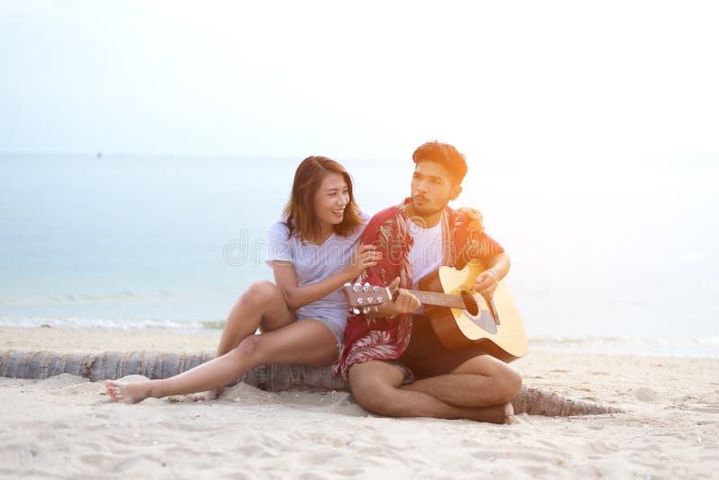 Het leuke Spaanse paar speelgitaar serenading op strand stock foto's
