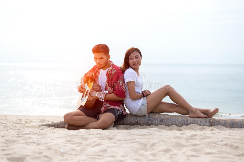 Het leuke Spaanse paar speelgitaar serenading op strand stock afbeelding