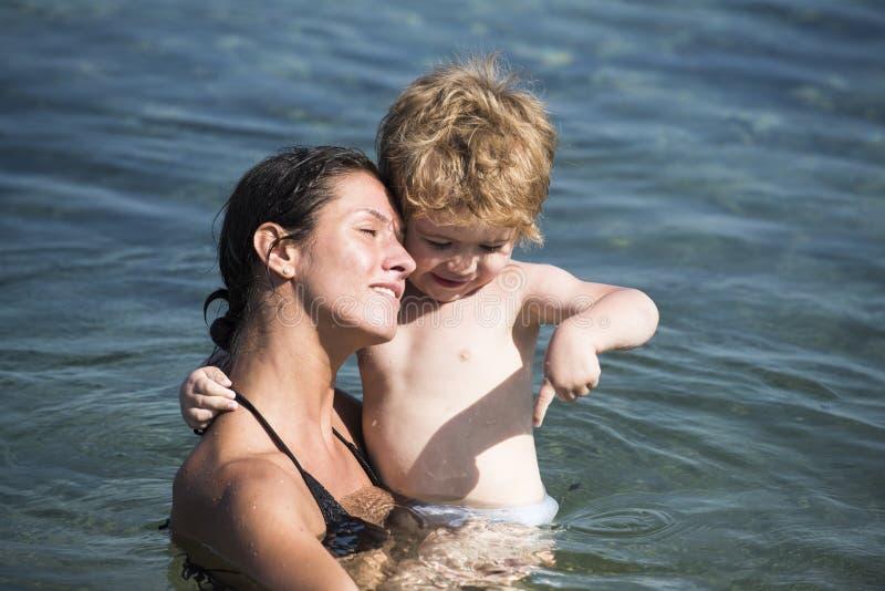 Het leuke spel van de kindjongen met water in oceaan, overzees Het concept van het moederschap De moeder vervoert zoon in handen, stock fotografie