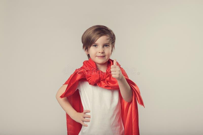 Het leuke superherojonge geitje geeft duimen op stock afbeelding