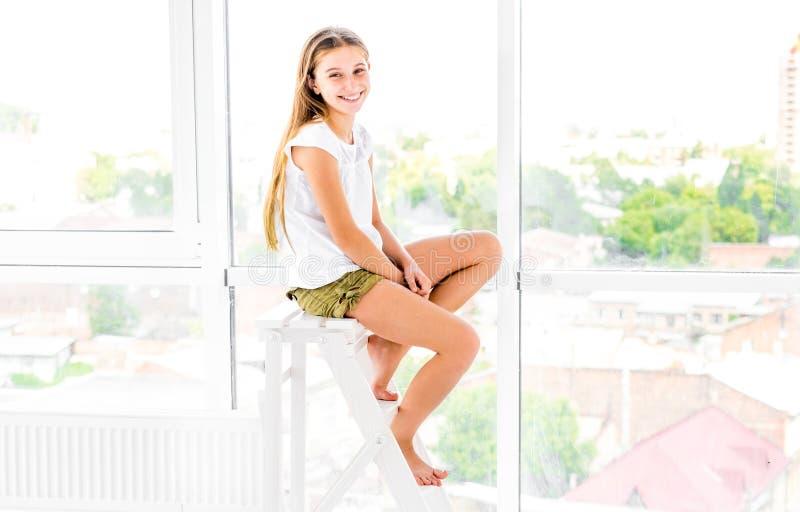 Het leuke tienermeisje zit op trapladder stock afbeeldingen
