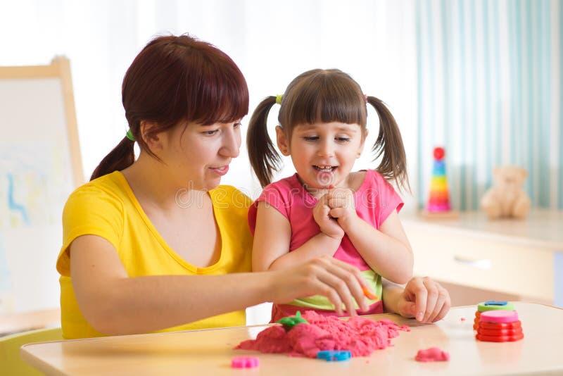 Het leuke van de kindmeisje en moeder spelen met kinetisch zand thuis stock afbeelding