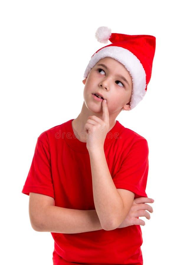 Het leuke in verwarring gebrachte kijken jongen, santahoed op zijn hoofd, met de vinger dichtbij de lippen Concept: Kerstmis of G royalty-vrije stock fotografie
