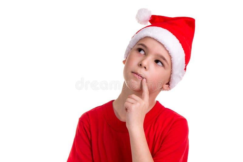 Het leuke in verwarring gebrachte kijken jongen, santahoed op zijn hoofd, met de vinger dichtbij de lippen Concept: Kerstmis of G royalty-vrije stock afbeeldingen