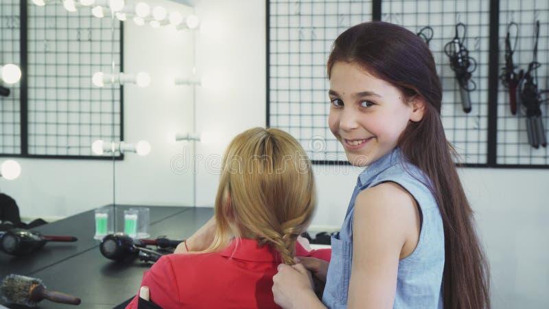 Het leuke vrolijke haar van het meisjevlechten van haar mamma die aan de camera glimlachen royalty-vrije stock afbeeldingen