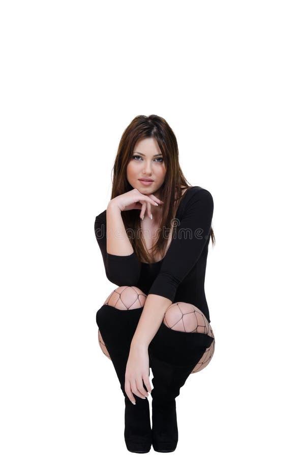 Het leuke vrouwelijke stellen in de studio gekleed in sexy bodysuit stock foto's