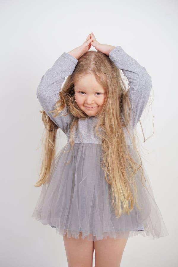 Het leuke weesmeisje bevindt zich en houdt haar handen over haar hoofd in de vorm van een huis, dromend van een flat, op een witt royalty-vrije stock afbeelding