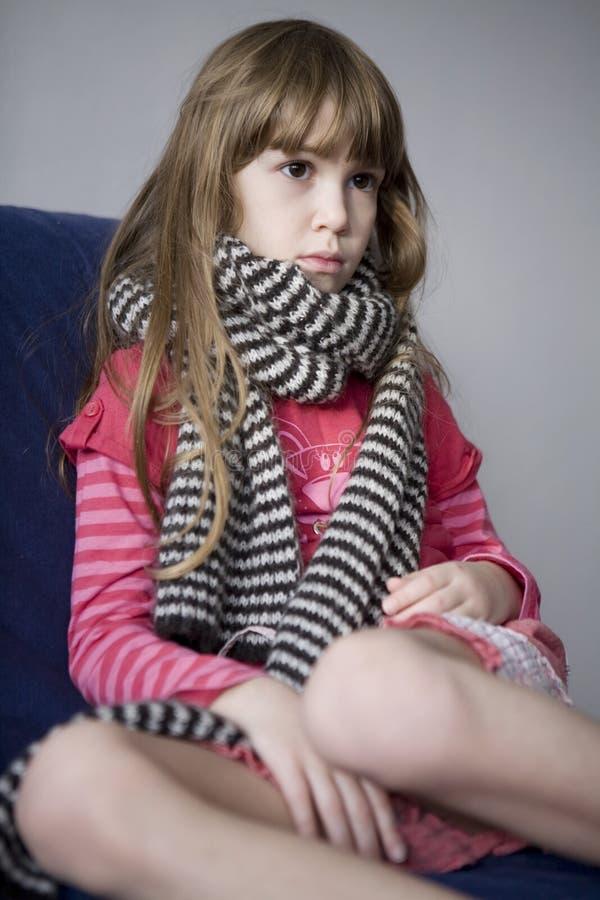 Het leuke zieke meisje van Llittle met sjaal. Keelpijn stock foto's