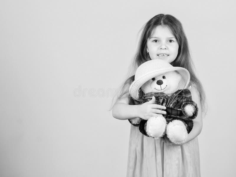 Het leukst ooit Het jong geitjemeisje koestert zorgvuldig zachte stuk speelgoed teddybeer beige achtergrond Tedere gehechtheid Kl royalty-vrije stock afbeeldingen