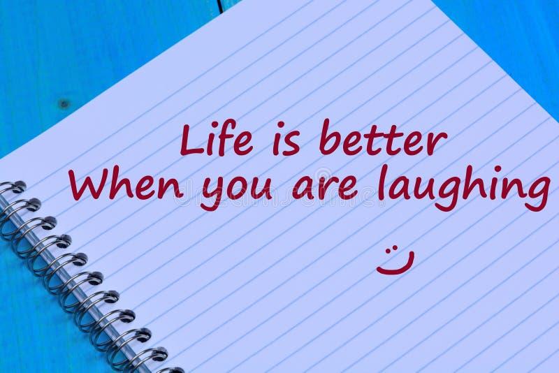 Het leven is beter wanneer u het lachen woorden op notitieboekje bent stock foto