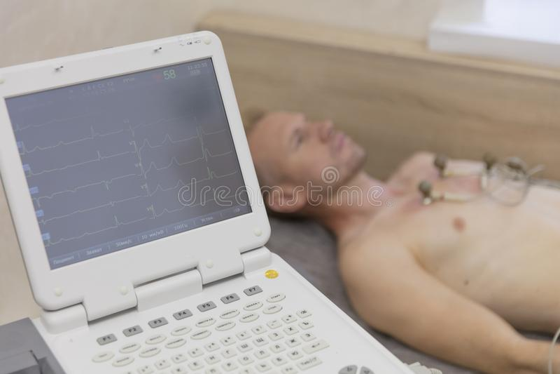 Het leven controlerende arts die met elektrocardiogrammateriaal cardiogram tot test maken aan mannelijke patiënt in het ziekenhui royalty-vrije stock fotografie