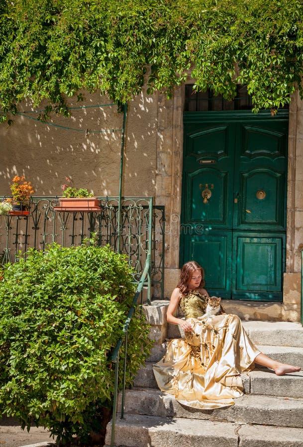 Het leven in de Provence. Vrouwenzitting op de portiek en het strijken van een kat royalty-vrije stock foto's