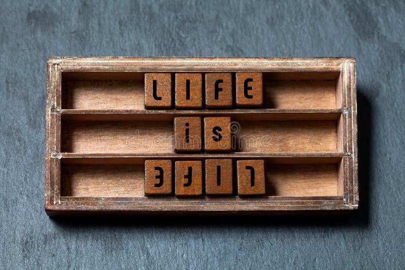 Het leven is het leven, tegenover tegenconcept Sjofel houten vakje, kubussen met oude stijlbrieven, Grijze steen geweven achtergr royalty-vrije stock foto's
