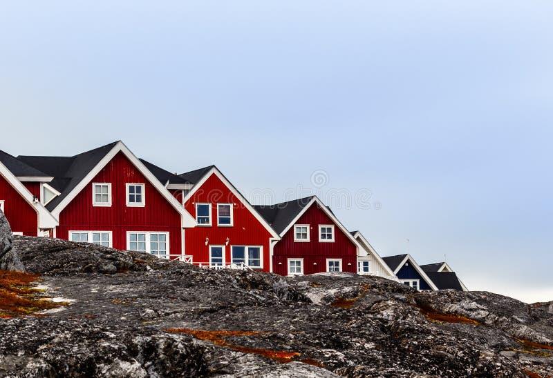 Het leven Inuit huizen die zich in de rij onder de rotsen Nuuk, Gr. bevinden stock afbeelding