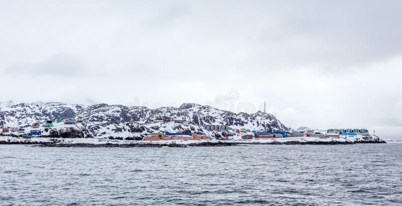 Het leven Inuit huizen op de steile helling in sneeuw bij de fjord wordt behandeld, Maniitsoq die royalty-vrije stock afbeeldingen