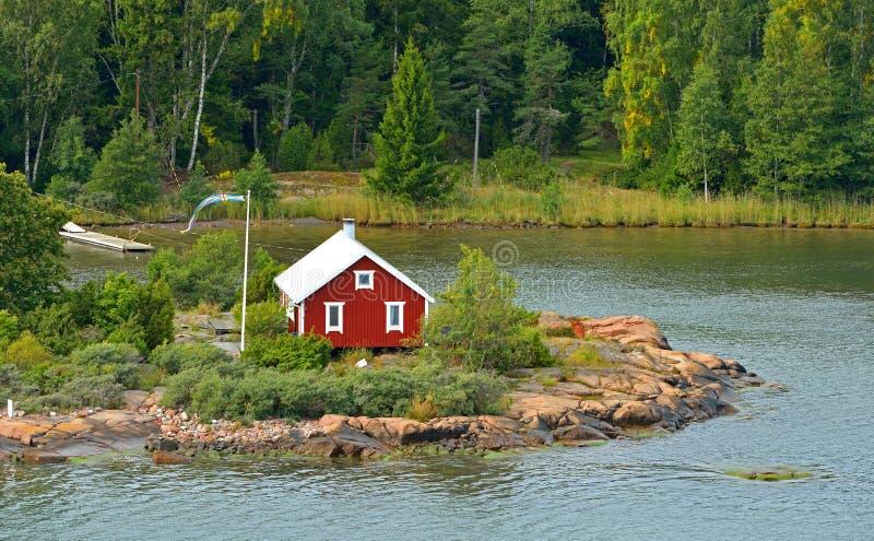 Het leven op kleine eilanden Rood blokhuis met vlag van Aland-Eilanden, Suomi stock fotografie
