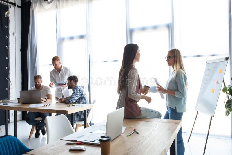 Het leven van het bureau Groep jonge bedrijfsmensen die en in creatief bureau samenwerken communiceren stock afbeelding