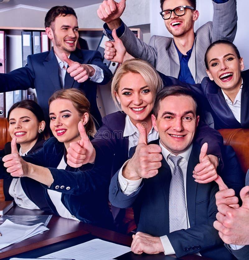 Het leven van het bedrijfsmensenbureau van teammensen is gelukkig met omhoog duim stock afbeeldingen