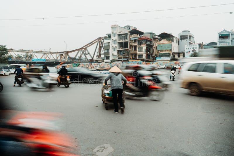 Het leven van Vietnamese verkoper in HANOI, VIETNAM De verkoper probeerde om de wegen in gek verkeer te kruisen royalty-vrije stock fotografie