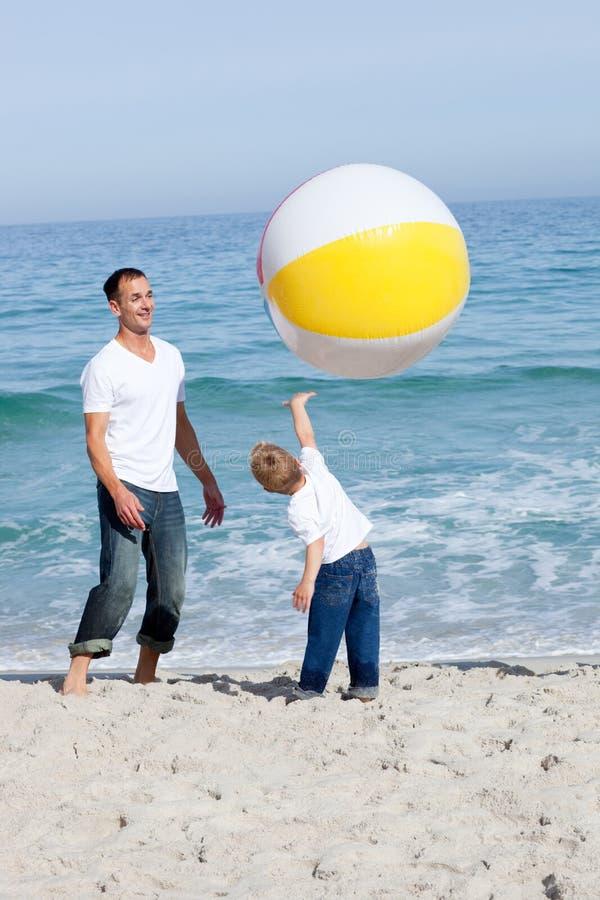 Het levendige familie spelen met een bal stock foto