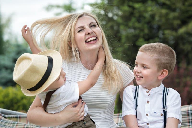 Het levensogenblik van gelukkige familie! Jonge moeder en twee mooie zonen royalty-vrije stock fotografie