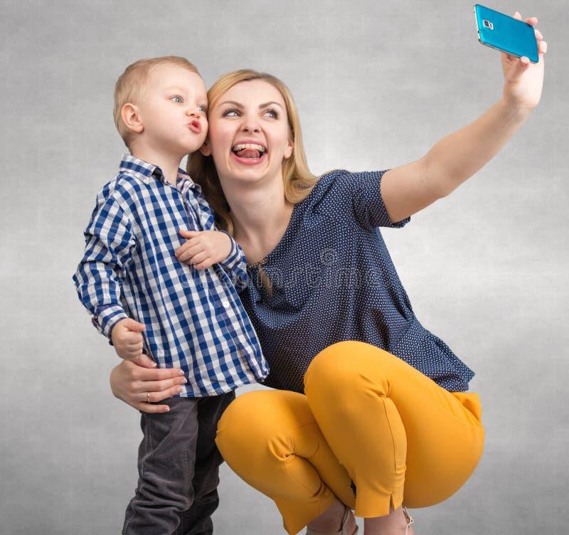 Het levensogenblik van gelukkige familie! Weinig jongen omhelst teder zijn moeder stock fotografie