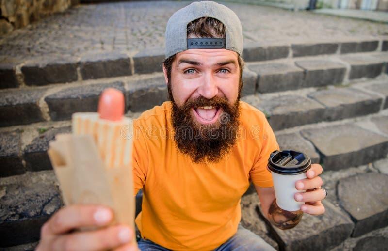 Het levenssmaken beter met hete keuken Hipster die traditionele hotdogkeuken hebben tijdens rust onderbreking Kaukasische kerel stock afbeeldingen