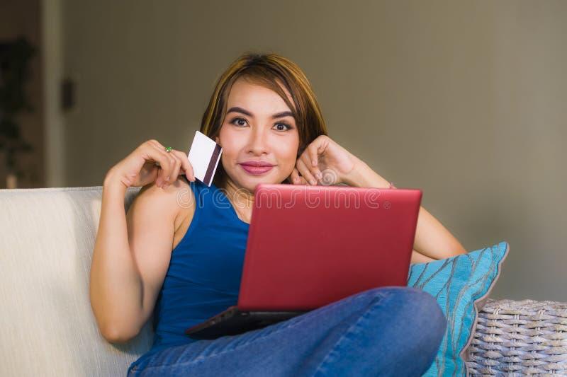 Het levensstijlportret van jonge mooie en gelukkige vrouw ontspande thuis de holdingscreditcard van de woonkamerlaag gebruikend l stock afbeeldingen