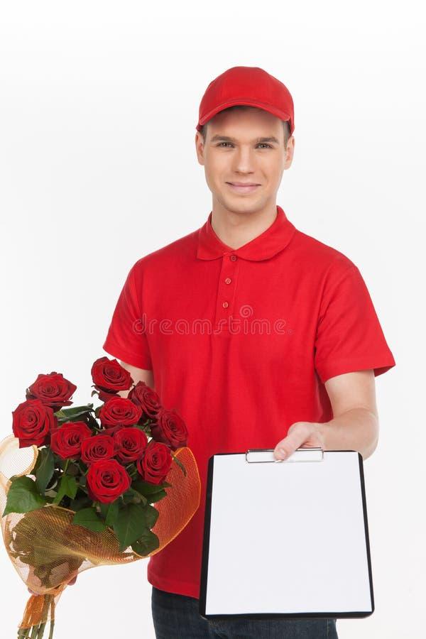 Het leveren van bloemen. Vrolijke jonge bezorger die uit a uitrekken royalty-vrije stock foto's