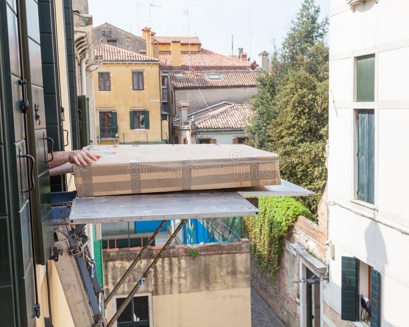 Het leveren van meubilair aan een eerste verdieping die een hijstoestel of een lift met behulp van dur stock afbeelding
