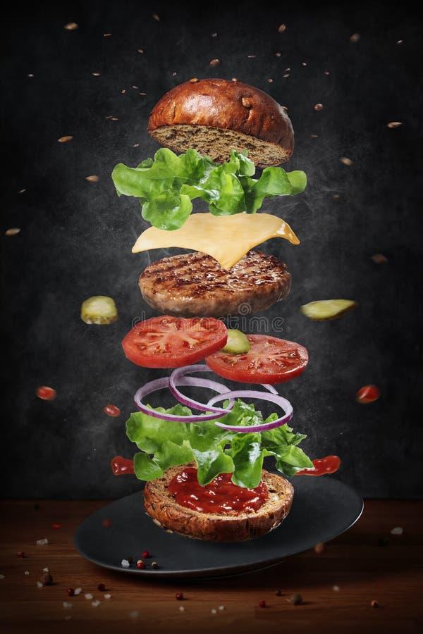 Het levitatie ondergaan van verse ingrediënten van heerlijke warme hamburger stock foto's
