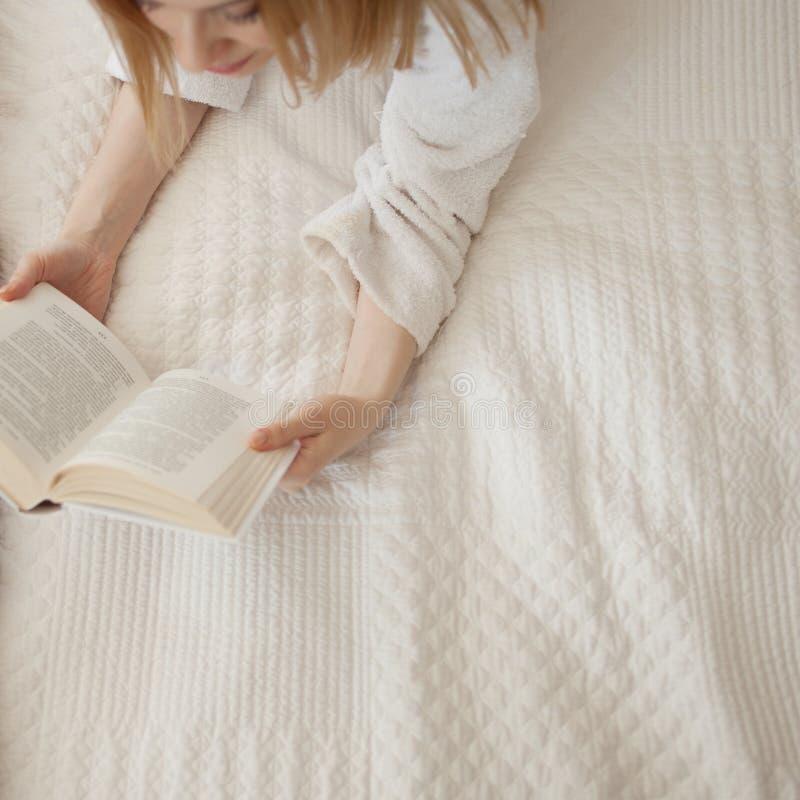 Het lezen in Bed Jong mooi blondemeisje die op het bed liggen en een boek lezen De hobby en ontspant stock foto