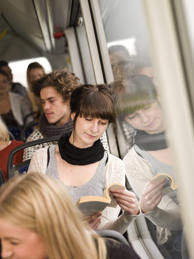 Het lezen bij de bus stock foto