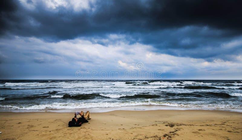 Het lezen bij het strand royalty-vrije stock afbeeldingen