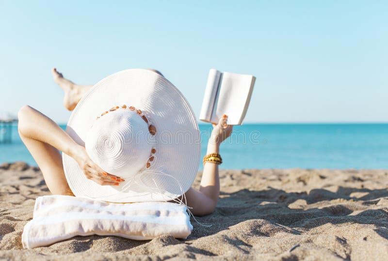Het lezen op strand stock afbeelding
