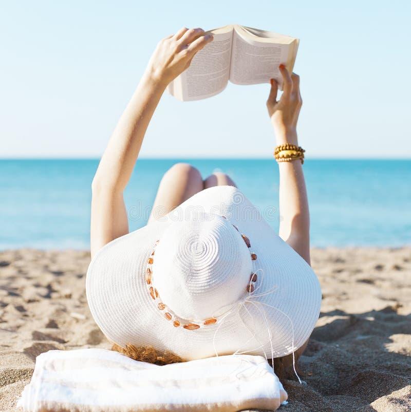 Het lezen op strand stock fotografie
