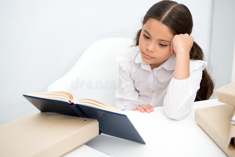 Het lezen van boring boek Het meisjeskind leest boek terwijl lijst witte achtergrond zit Schoolmeisje die en boek bestuderen leze royalty-vrije stock afbeeldingen