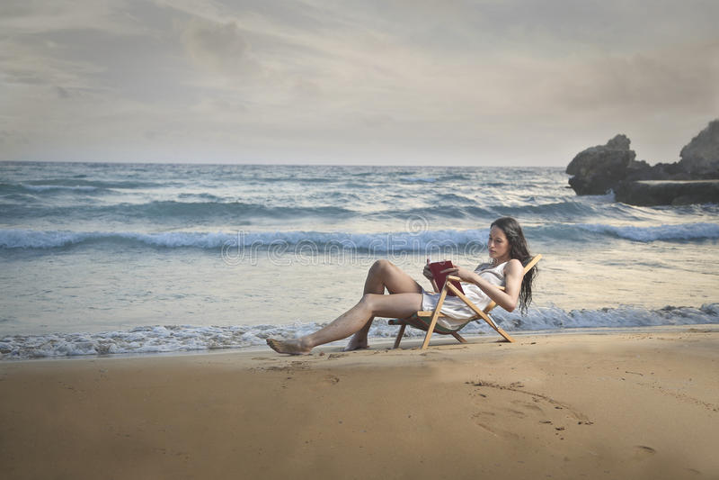 Het lezen van een boek bij de kust stock foto's