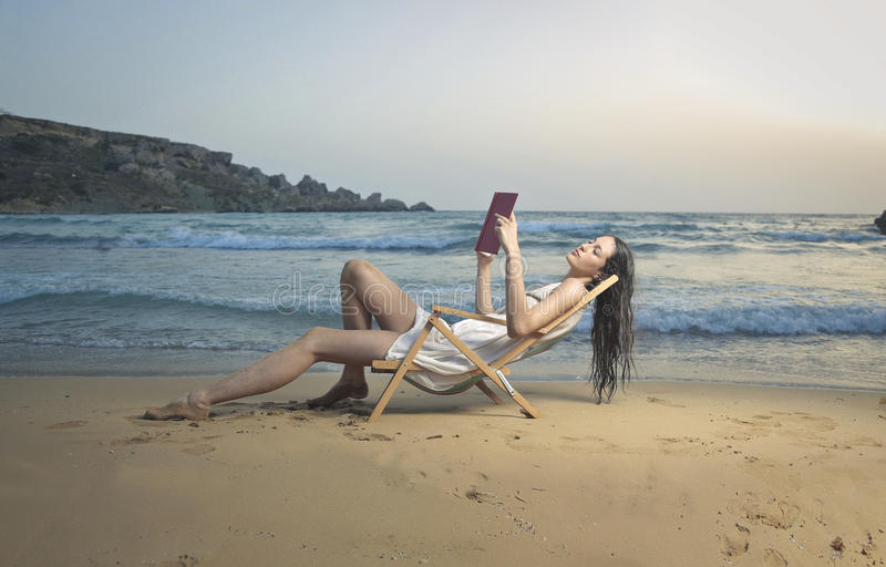 Het lezen van een boek bij de kust royalty-vrije stock afbeelding
