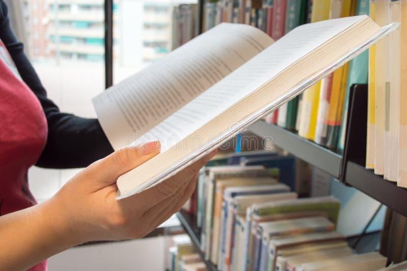 Het lezen van een boek in een bibliotheek stock afbeelding