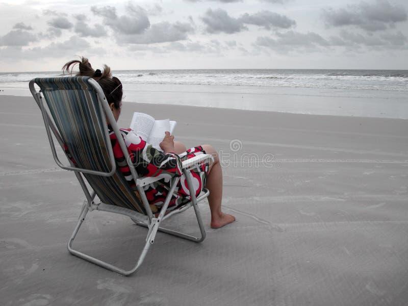 Het lezen van een boek in het strand stock afbeelding