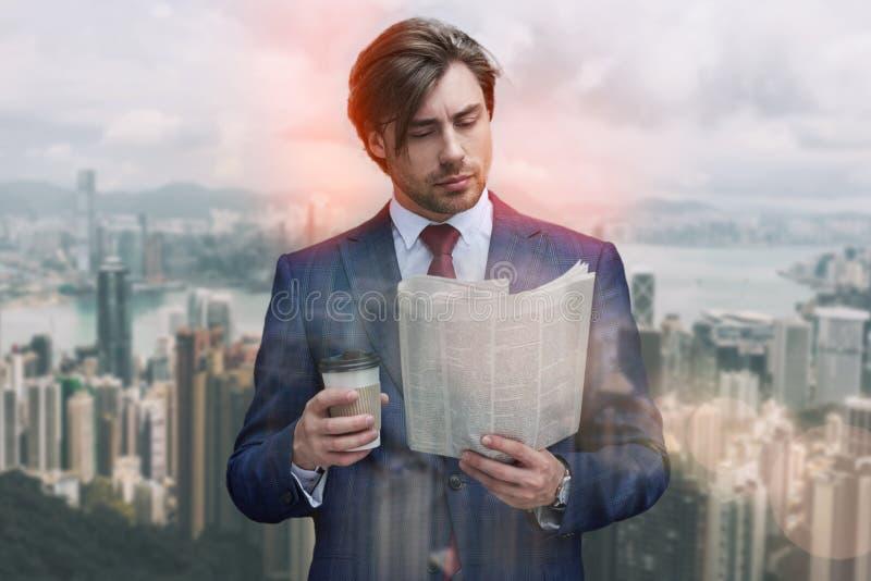 Het lezen van vers nieuws Zekere jonge zakenman in de krant van de kostuumlezing en holdingskop van koffie terwijl status stock foto