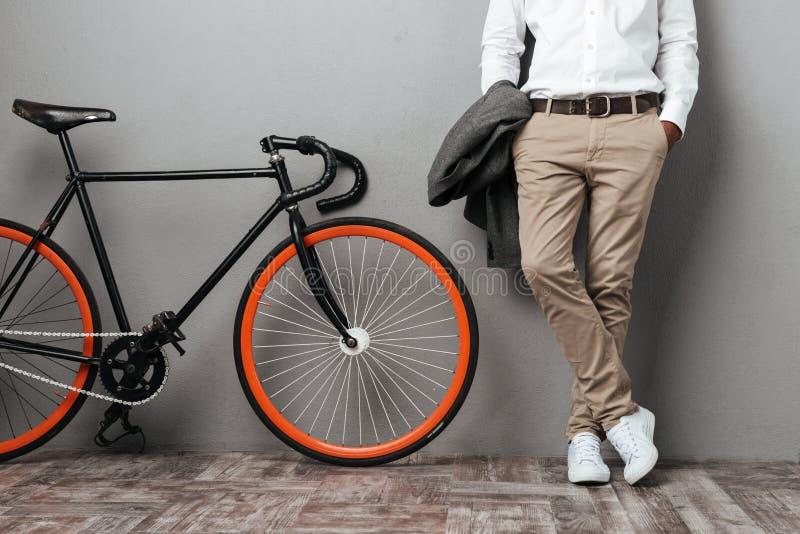 Het lichaam die van geklede halve mensen zich dichtbij een fiets bevinden royalty-vrije stock afbeelding