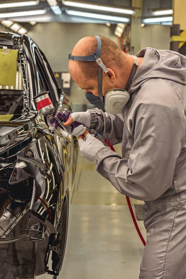 Het lichaam van de werknemersauto het schilderen de winkel voert het schilderen element uit stock fotografie